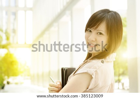 Young Asian female business people smiling and holding file folder, standing in an office environment, beautiful golden sunlight background. - stock photo