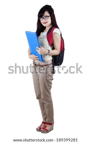Young asian female college student holding documents and standing over white background. shot in studio