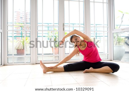 Young Asian female doing stretching exercise in a calm and peaceful environment - stock photo
