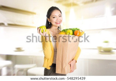 Young Asian female hand holding shopping paper bag filled with fruits and vegetables in kitchen.