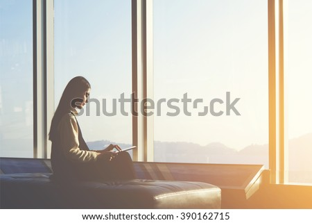 Young Asian female is watching news on digital tablet, while is sitting in airport interior against window with copy space area.Attractive Chinese woman is using portable computer and waiting her fly  - stock photo