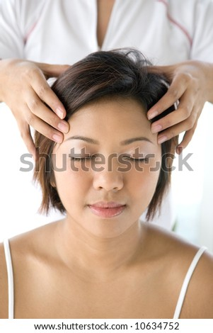 Young Asian female receiving gentle head massage as part of holistic therapy treatment in spa lifestyle - stock photo