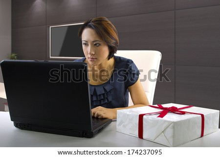young asian female shopping online for gifts - stock photo