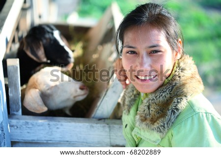 young asian female smiling in goat barn - stock photo