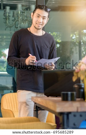 young asian freelance man standing with smiling face in home office happiness emotion