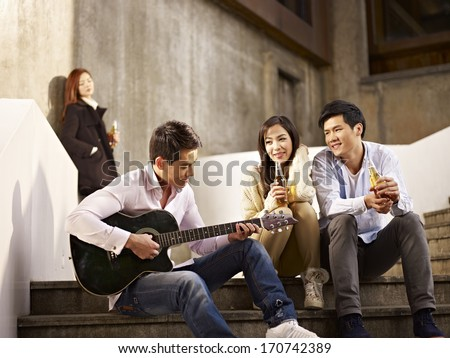 young asian friends lovers sitting on steps enjoying beer and music. - stock photo