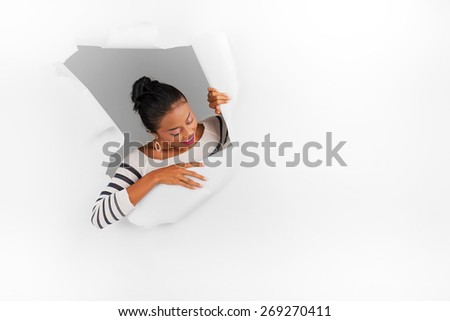 Young Asian girl breaking through white paper - stock photo