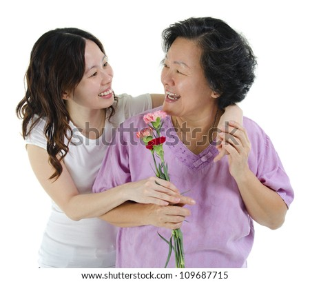 Young Asian girl carnation flower to her mum, over white background - stock photo