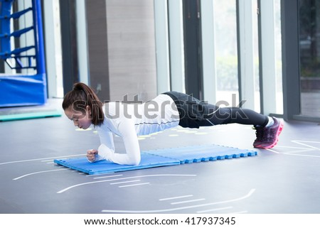 young asian girl doing yoga in modern gym