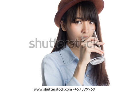 Young asian girl drinking water, holding a glass of water, isolated on white background.