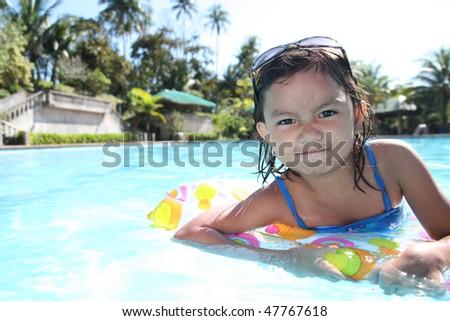 young asian girl enjoying at the swimming pool - stock photo