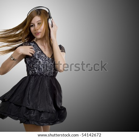 Young Asian girl listening to music on headphones with sexy dress - stock photo