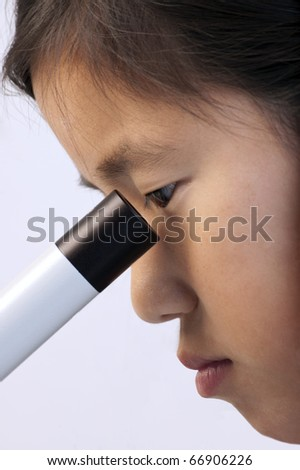 Young Asian girl looking into a microscope - stock photo