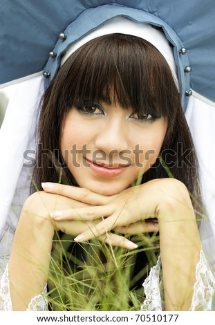 young asian girl lying on the grass and smiling at camera wearing unique costume