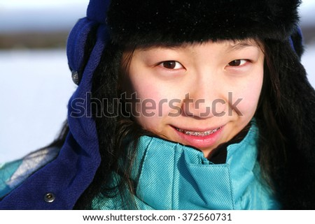 Young Asian girl outdoors in winter. - stock photo