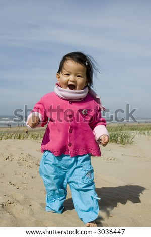 Young Asian girl playing on the beach. - stock photo