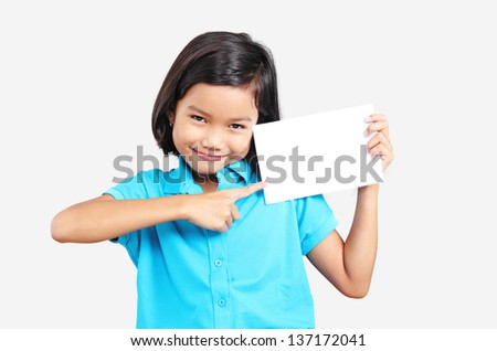 Young asian girl pointing to a white empty white card. - stock photo