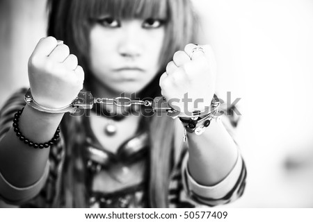 Young asian girl showing handcuffs on her wrists - stock photo