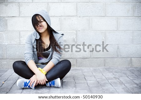 Young asian girl sitting in urban background - stock photo