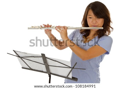 Young asian girl standing up reading sheet music and playing - stock photo