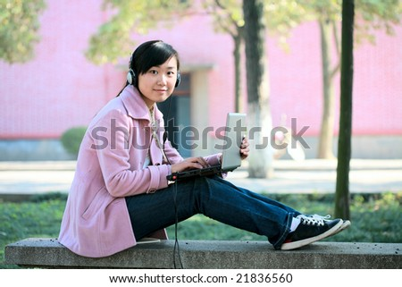 young asian girl study on laptop in college - stock photo