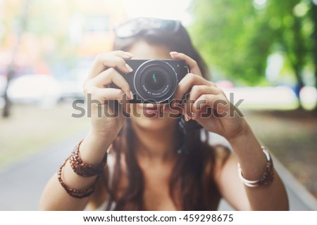 Young asian girl taking photo outdoors with digital camera. Selective focus at lens, unrecognizable person. Young female tourist having fun in summer park. Lifestyle portrait, soft toned - stock photo