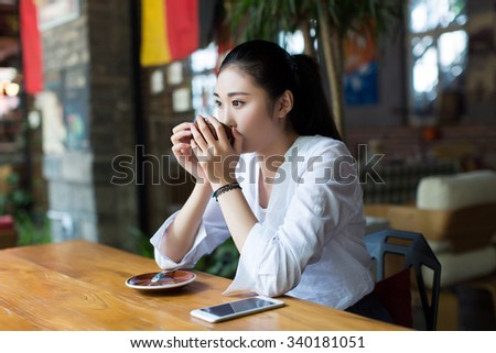 young asian girl use mobile phone for search information in coffee shop