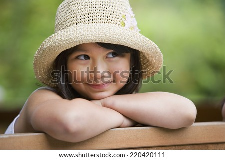 Young Asian girl wearing straw hat and smiling outdoors - stock photo