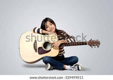 Young asian girl with a acoustic guitar, Isolated on grey background - stock photo