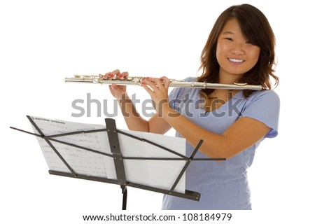 Young asian girl with a silver flute smiling - stock photo