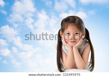 Young Asian girl with smile on her face sitting outdoor in summer day, blue sky background - stock photo