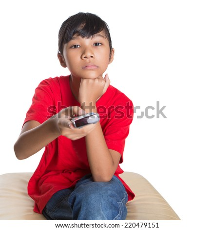 Young Asian girl with television remote control device over white background - stock photo