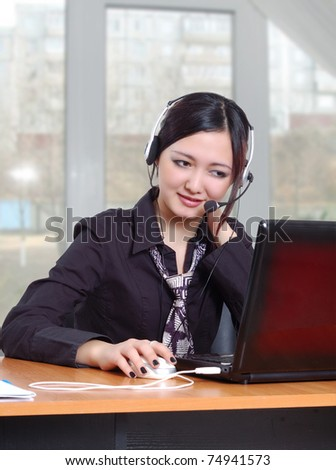Young Asian girl working at a computer and communicates