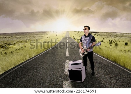 Young asian guitarist playing solo guitar on the road, shot outdoors - stock photo