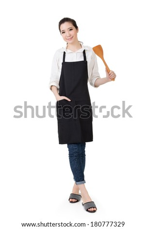 Young Asian housewife hold a spatula in apron, full portrait isolated on white background. - stock photo