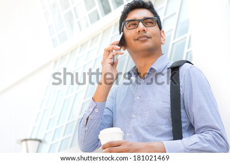 Young Asian Indian businessman on the phone with a cup of coffee in morning, male business man, real modern office building as background. - stock photo