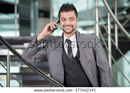 Young Asian Indian businessman standing on office background and talking on the phone - stock photo