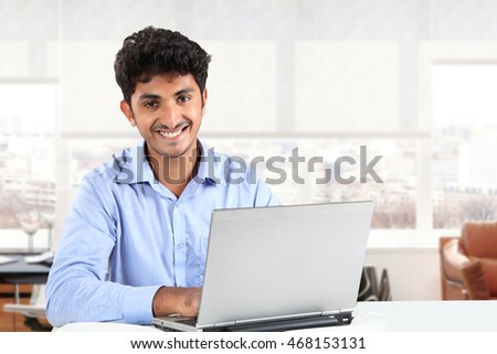 Young Asian Indian Businessman working on laptop in office