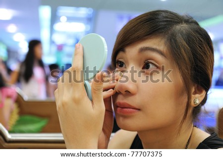 Young asian lady applying make up - stock photo