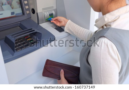 Young Asian lady at an ATM