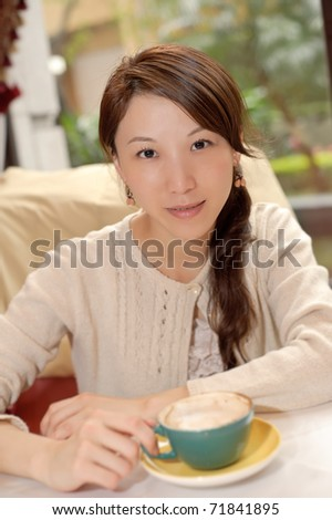 Young Asian lady with cup of coffee in restaurant. - stock photo