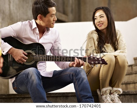 young asian lovers sitting on steps playing guitar and singing - stock photo