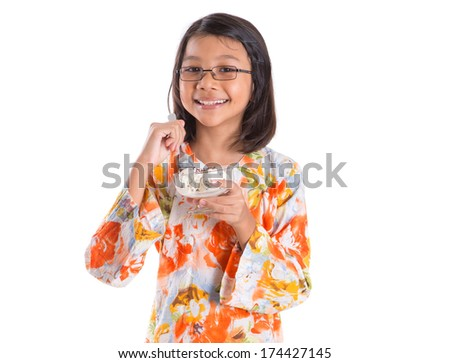 Young Asian Malay girl enjoying a bowl of ice cream over white background