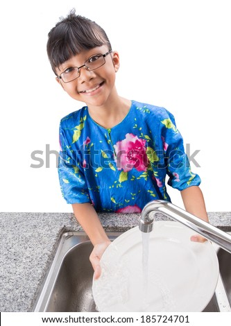 Young Asian Malay girl in washing white plate at the kitchen sink - stock photo