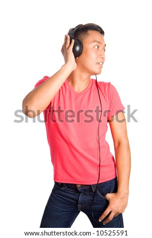 Young Asian malay male listening to music through his headphone, isolated
