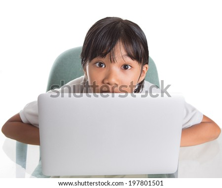 Young Asian Malay school girl hiding behind her laptop