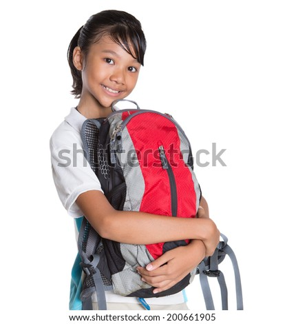 Young Asian Malay school girl in school uniform with red backpack over white background