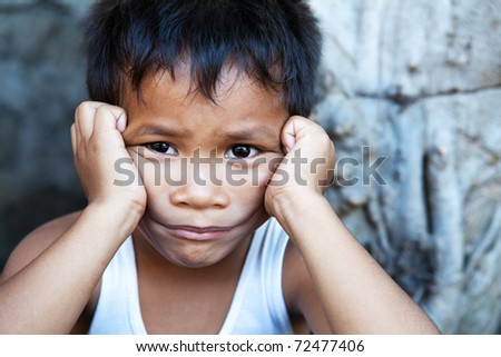Young Asian male against wall - Poverty in the Philippines - stock photo