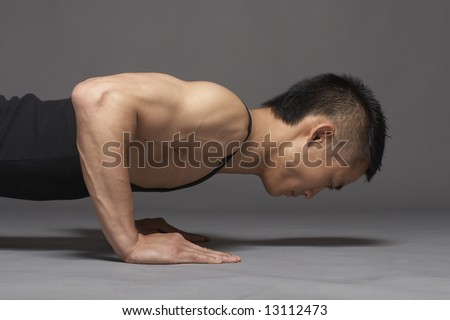Young asian man doing pushup over gray background