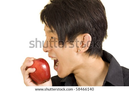 Young Asian man eating apple - stock photo
